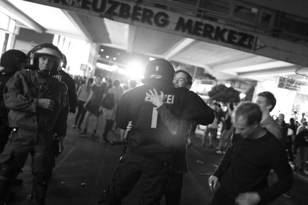 Ein Bild der Ausstellung: Ein Polizist umarmt einen Mann.